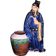 Chinese Export Mudman of an Old Sage standing in front of a large barrel