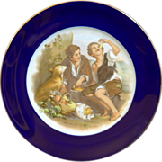 "Rosenthal Germany Figural cabinet plate ""Melon Eaters"" with a cobalt blue border and gilded rim."