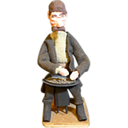 Hand carved and painted folk art or tramp art figurine of a man sitting panning for gold.