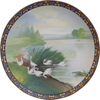 Hand Painted Nippon wall plate, ornately decorated with a geometric border around a matt finish, Lake scene