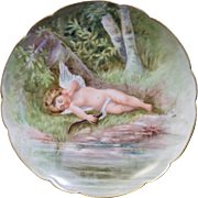 Fantastic Haviland Limoges hand painted scalloped edge plate with Cupid lying near a stream in the woods.