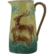 Yellow ground majolica pitcher with deer, grass and ferns near oak trees