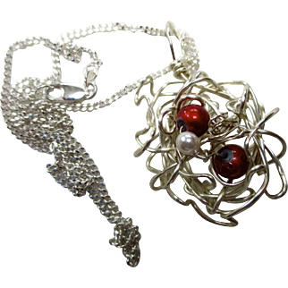 Handmade, origianl, silver plated wire nest with two red glass beads and a pearl; wire nest and  chain