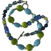 Artisan necklace: lucite greens and blues: silver barrels: toggle clasp: 23""