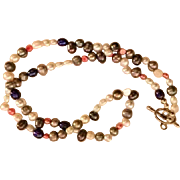 Artisan Necklace: 24 inches of multicolored freshwater pearls: red, pink, silver, ivory, blue tan, closed with a silver plated toggle