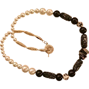 Artisan Necklace: Black and White different beads: a glass focal bead: graduated white glass pearls: silver plate filagree longs: a modern toggle: 22 inches