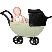 Adorable small vintage doll in buggy