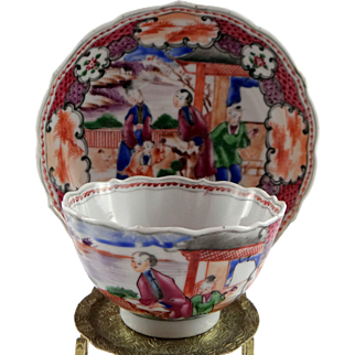 Chinese export porcelain cup and saucer, c. 1800, in the Mandarin palette, scalloped edge with Chinese scenes