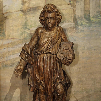 A Carved 17th Century French Statue of an Angel Holding a Candlestick