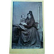 Fascinating CDV portrait photograph of older Spanish woman wearing mantilla hat and fair skinned child on table