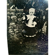 Outdoor tintype young boy wearing dress posed by painted stone wall floral prop