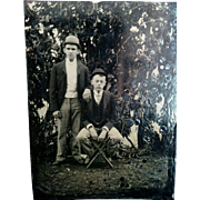 Outdoor tintype two young men brothers? posed in front of trees or vine backdrop circa 1890s