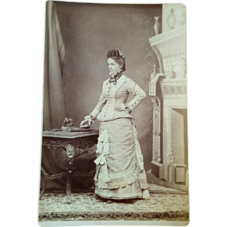 1880s Cabinet card photograph of a beautiful & fashionably dressed young woman posed by ornate table