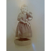 Circa 1890s Cabinet card photograph showing cute young girl holding an unusual doll baby