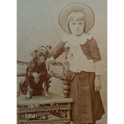 Little girl wearing hat & posed by small dog in wicker chair circa 1890's Victorian photograph