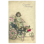 Undivided Postcard of Tinted Photo of Cupid in Car with Flowers