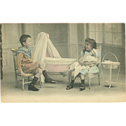 Undivided Tinted Photo Postcard of Young Boy and Girl with Doll Playing House