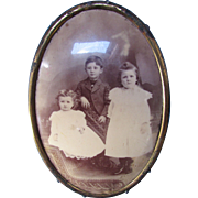 Trio Victorian Era Children in Sepia Tone Photograph Framed in Oval Metal
