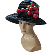 Bucket Style Hat in Black Cellophane with Dangling Red Cherries Fashioned by Betty Terry