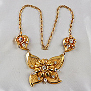Large floral necklace with a flower & bright crystal rhinestones gold tone