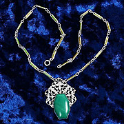 Art Deco pendant necklace swirling opaque green glass stone