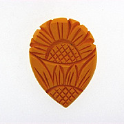 Deeply carved sunflower Bakelite dress clip