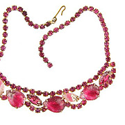 Bright pink vintage rhinestone Choker Necklace with molded leaves and givre stones in a gold tone finish