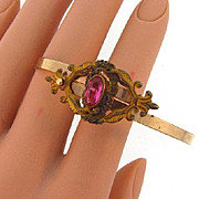 Vintage pivoting wrap around Bracelet topped with scrolling Victorian style centerpiece and pink glass stone