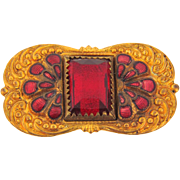 Early 1900's small gold tone Brooch with center red glass stone flanked by a red enamel design