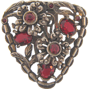 Vintage pot metal Dress Clip in a raised floral design with red glass stone