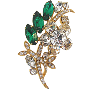Signed Weiss rhinestone Brooch in a floral spray with crystal and green stones