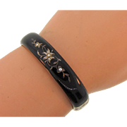 Early black enamel on silver tone bangle hinged Bracelet with floral design and seed pearls