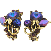 Signed Hollycraft clip back earrings in a floral design with purple rhinestones