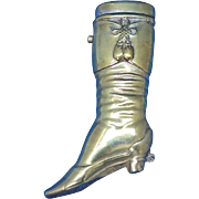 Figural cowgirl's riding boot match safe, brass, c. 1895