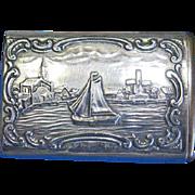 Slide type match safe, Dutch harbor scene with sailboat, windmill, church; 830 silver, c. 1895