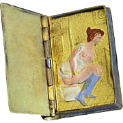 """Semi nude lady seated on potty match safe, book-shaped marked """"Guide"""", leather covered, cold painted, c. 1890"""