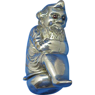 Figural dwarf with red glass eyes sitting on a chamber pot match safe, nickel plated brass, c. 1890
