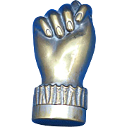 """Match safe, figural hand with thumb folded under a finger, brass, c. 1890.  """"The fig sign"""""""