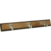 Wooden plank with three aluminum hooks.