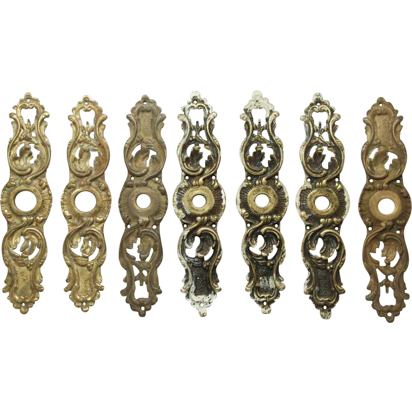 Set of seven ornate bronze back plates with keyhole