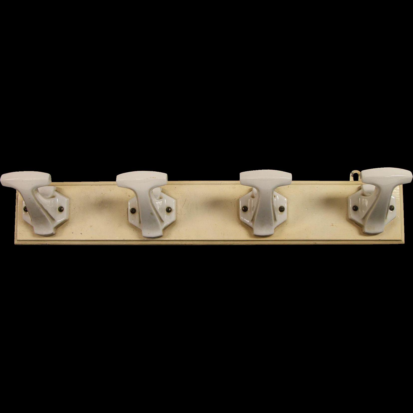 Four ceramic hooks on wood plank