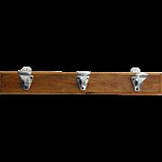 Three aluminum hooks on plank