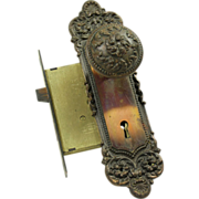 Ornate pressed brass knob set complete with lock and plates