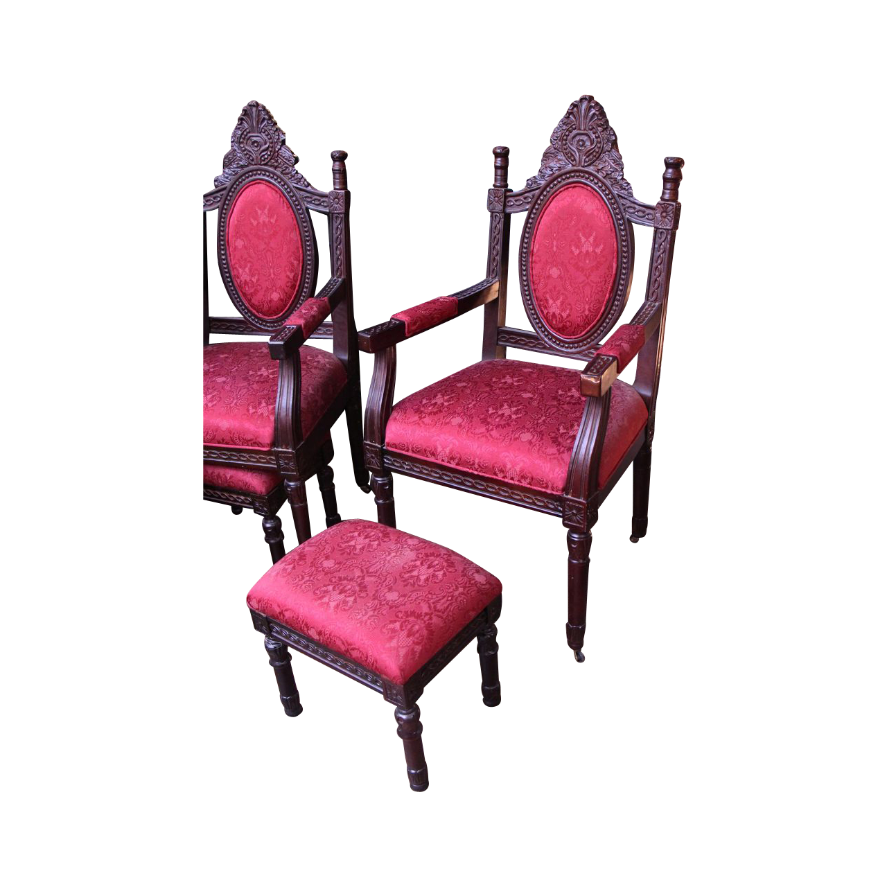 Pair of ornate red cushioned chairs with matching foot stool