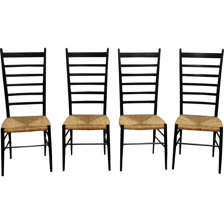 Set of four black ladder back chairs with wicker seat