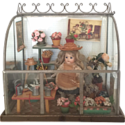 Antique glass garden doll's house with beautiful all-bisque German doll ca. 1910