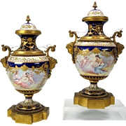 Pair of Sevres lidded urns with Women & Cherubs signed with bronze mounts