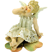 Victorian bisque Dresden lace figure of a Cherub Angel sitting on a 4 leaf clover