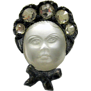 Antique tiny carved moonstone pin of a face under a paste bonnet