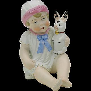 Vintage German bisque figure piano baby with velveteen rabbit toy